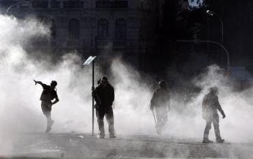 A masked youth throws stones at riot policemen during riots in Athens